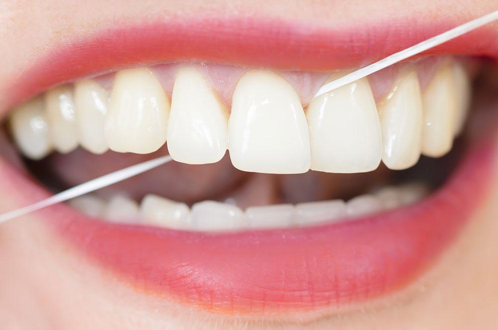Frauenmund mit schönen weißen Zähnen und Pflege mit Zahnseide
